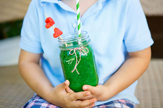 child holding a glass of juice